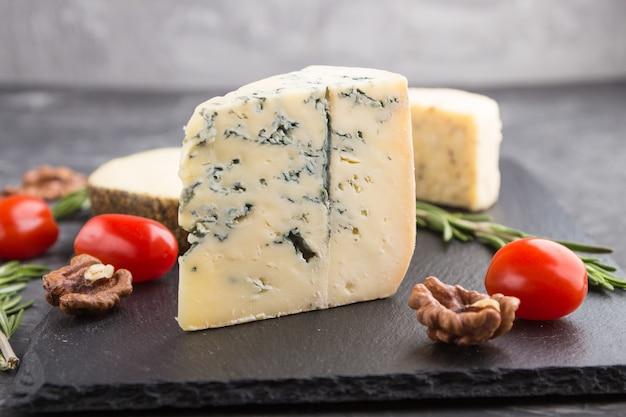 Fromage bleu et divers types de fromage au romarin et tomates sur une ardoise noire sur une surface de béton noir