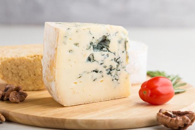 Fromage bleu et divers types de fromage au romarin et tomates sur planche de bois sur une surface en bois blanc