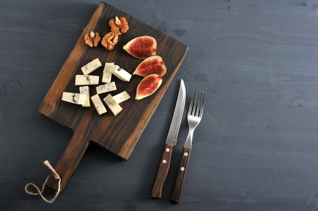 Fromage bleu, figues fraîches et noix sur une planche de bois et un couteau