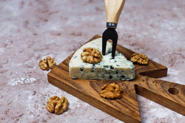 Fromage bleu sur une planche à découper en bois avec du miel et des noix