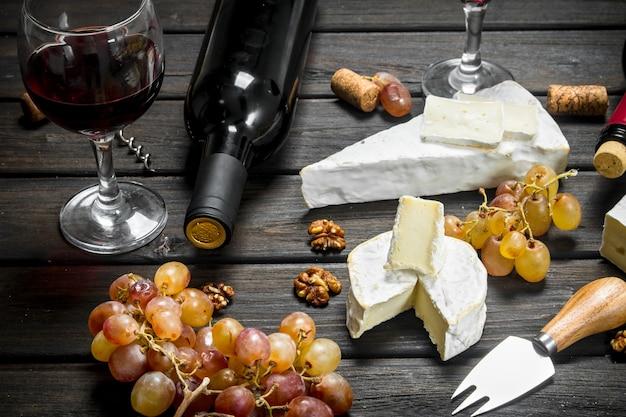 Fromage brie au vin rouge, noix et raisins sur table en bois.