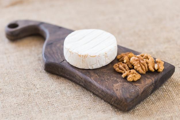 Fromage brie ou camembert aux noix et raisins sur une planche de bois