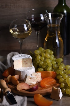 Fromage brie, camembert aux raisins blancs, kakis et prunes tranchés, un excellent apéritif pour le vin