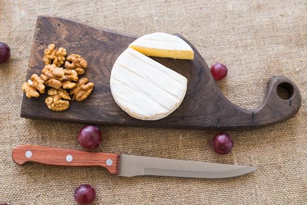 Fromage brie ou camembert avec des noix et des raisins sur une vue de dessus de planche de bois