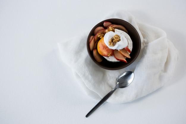 Fromage brie servi avec des tranches de fruits et de noix dans un bol