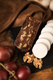 Fromage brun et blanc avec noix et raisins sur ardoise noire