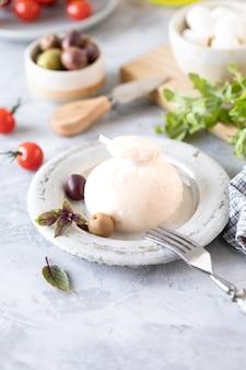Fromage burrata italien sur une assiette blanche ronde et ingrédients pour salade