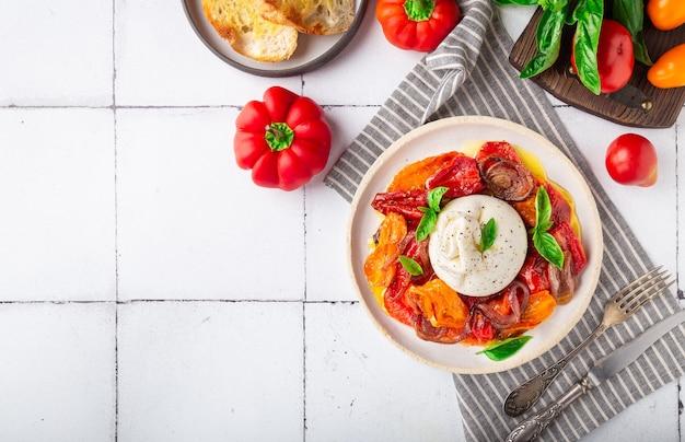 Fromage burrata avec tomates cuites au four, poivron rouge et basilic frais sur fond de carreaux blancs