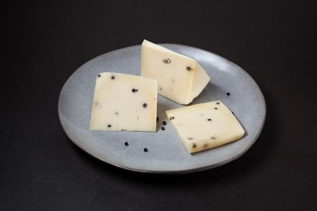 Fromage caciotta italien traditionnel avec du poivre noir sur plaque grise.