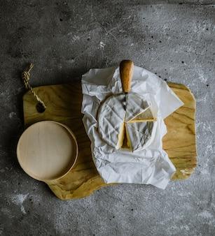 Fromage camambert sur planche de bois avec couteau à fromage et plateau en bois