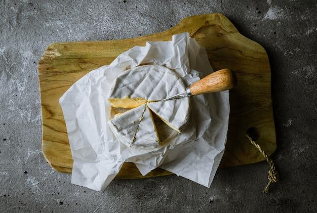 Fromage camambert sur planche de bois avec couteau à fromage