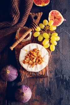 Fromage camembert aux figues, noix, miel et thym servi pour un dîner en dark key sur table en bois dans un style rétro. image tonique. vue de dessus.