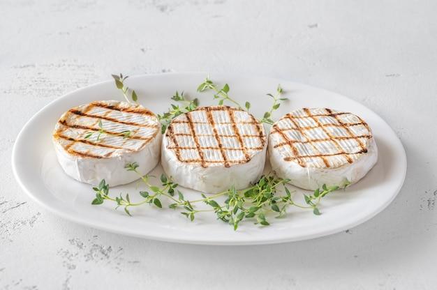 Fromage camembert grillé au thym frais sur l'assiette