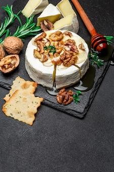 Fromage camembert et noix sur une planche de service en pierre