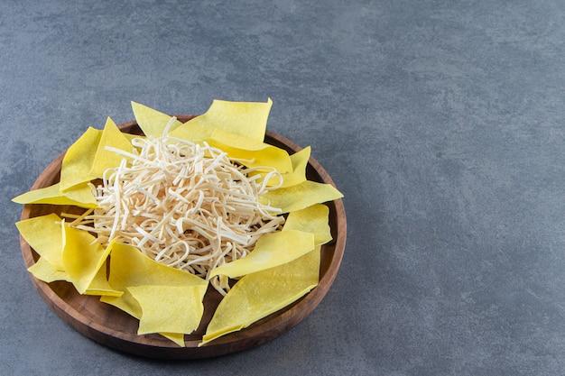 Fromage cecil et feuilles de lasagnes sur une assiette en bois, sur le fond de marbre.