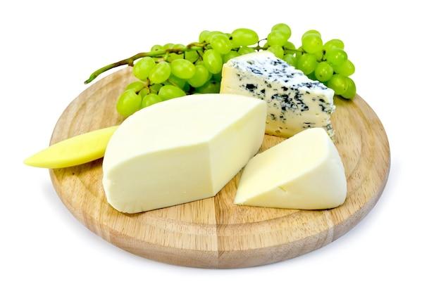 Fromage avec champignon, suluguni, une grappe de raisin, un couteau sur une planche de bois ronde isolé sur fond blanc