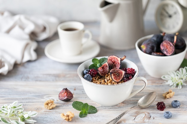 Fromage cottage aux figues, baies, miel. tasse de café et cafetière. petit déjeuner. table en bois.