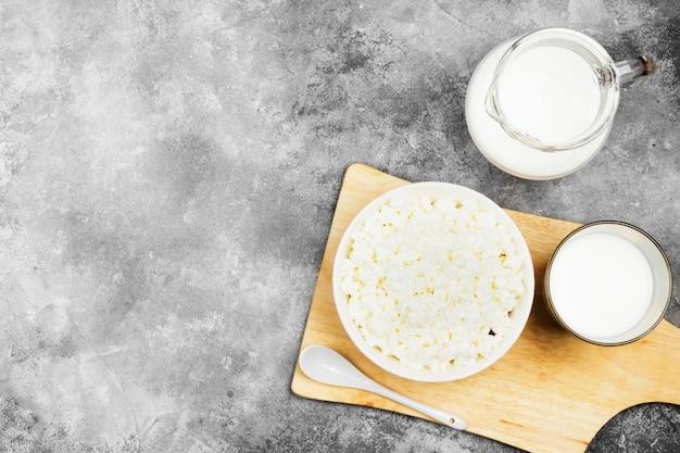 Fromage cottage dans un bol sur une planche à découper en bois et du lait dans un verre