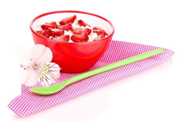 Fromage cottage dans un bol rouge avec des fraises tranchées isolated on white