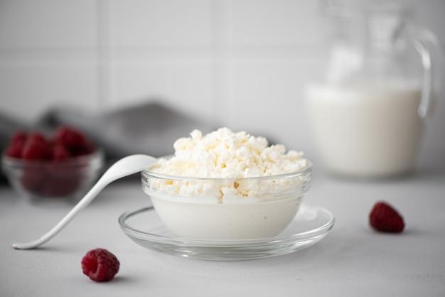 Fromage cottage fait maison avec du lait et des framboises dans un bol en verre sur un tableau blanc