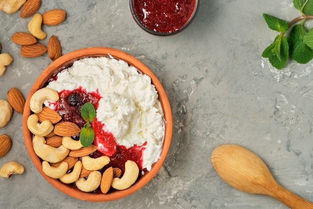 Fromage cottage frais avec de la crème sure, de la confiture de canneberges et des noix dans un bol en argile traditionnel