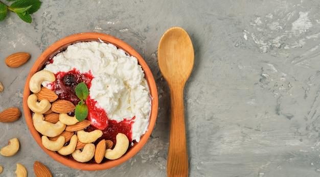 Fromage cottage frais friable avec crème sure, confiture de canneberges et noix dans un bol en argile traditionnel, à côté d'une cuillère en bois