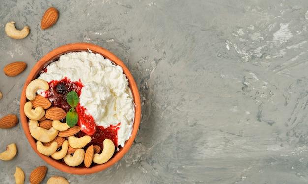Fromage cottage frais friable avec de la crème sure, de la confiture de canneberges et des noix dans un bol d'argile traditionnel sur fond gris
