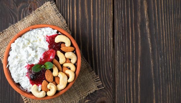 Fromage cottage frais friable avec crème sure, confiture de canneberges et noix dans un bol d'argile traditionnel sur table en bois
