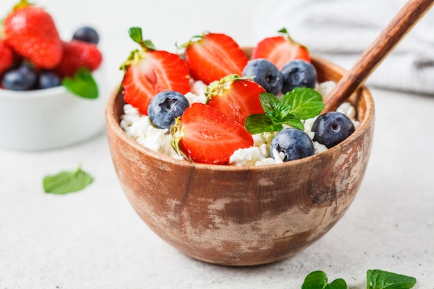 Fromage cottage avec des fraises et des bleuets dans un bol en bois