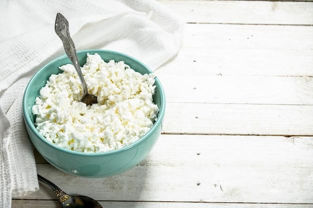 Fromage cottage de lait frais dans un bol. sur une table en bois blanche.