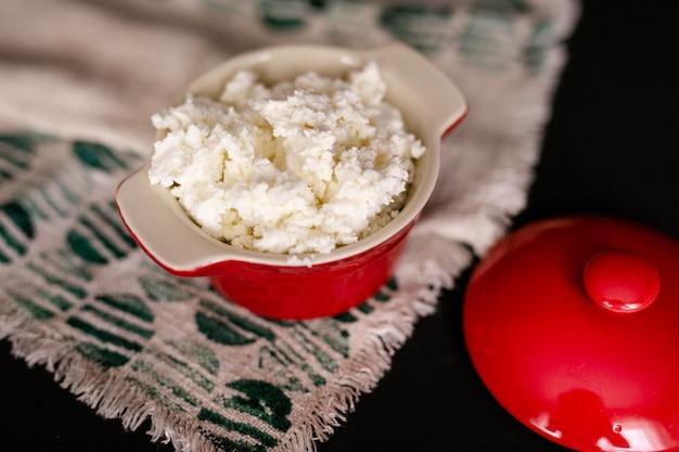 Fromage cottage produit laitier dans un bol en céramique brun avec une cuillère sur une table en bois vintage