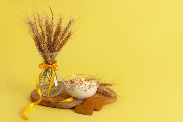 Fromage cottage saupoudré de miettes de biscuits, biscuits à la cannelle en forme de coeur, vase en verre, épis de blé sur une planche de bois sur une surface jaune