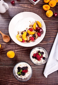 Fromage cottage et yaourt avec du gronala, des baies et des fruits à l'abricot pour un petit-déjeuner sain. vue de dessus.