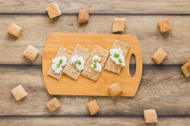 Fromage à la crème fraîche sur du pain croustillant sur la planche à découper du bureau