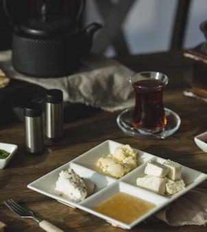 Fromage à la crème, miel et beurre avec un verre de thé