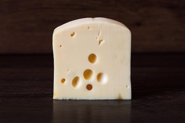 Fromage à la crème à pâte dure sur un fond en bois foncé. nourriture délicieuse et saine
