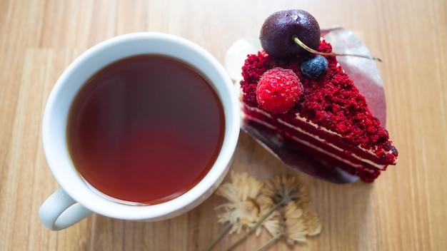 Fromage à la crème velours rouge avec du café noir dans du verre blanc, des fleurs séchées sont placées à proximité, fond en bois.