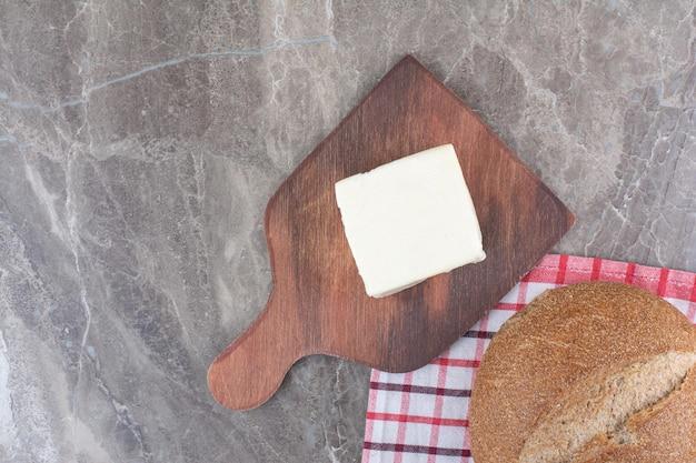 Fromage avec du pain brun sur planche de bois. photo de haute qualité
