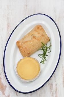 Fromage avec du pain sur une plaque blanche