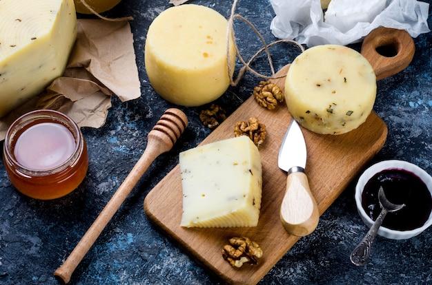 Fromage fait maison avec du miel, des fruits, des biscuits et des noix sur la table. produits laitiers frais, aliments biologiques sains. délicieux apéritif.