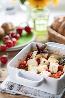 Fromage feta au four avec tomates cerises au basilic et huile d'olive. cuisine nationale grecque.