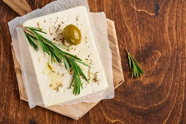 Fromage feta au romarin, herbes, olives et huile d'olive sur une planche à découper en bois sur la vieille table en bois. fromage maison grec traditionnel.