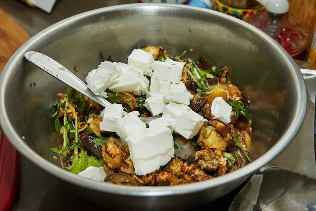 Fromage feta, aubergines au four et roquette dans un saladier. recette pas à pas.