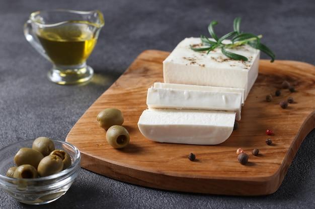 Le fromage feta est situé sur une planche de bois avec des olives, du romarin et de l'huile d'olive sur fond gris foncé