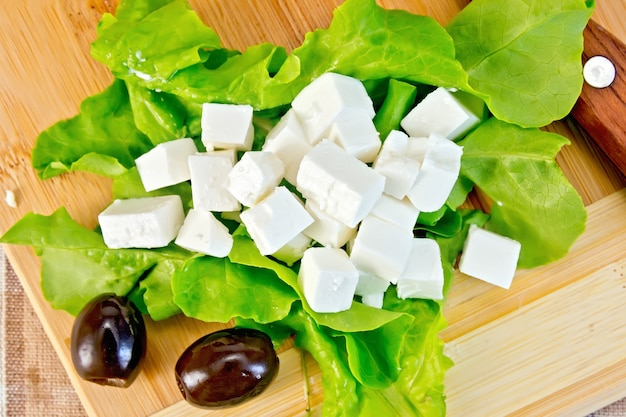 Fromage feta, laitue, olives, couteau sur fond planche de bois et tissu