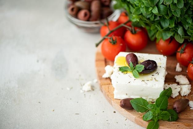 Fromage feta maison avec de l'huile d'olive, des tomates et du basilic sur une planche de bois