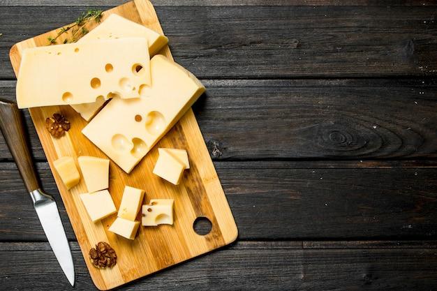 Fromage frais aux noix sur une planche en bois sur une table rustique.