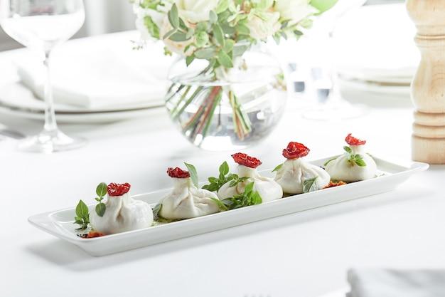 Fromage frais burata avec tomates et herbes sur plaque blanche.