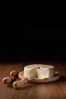Fromage, fromage minas du brésil sur une plaque en bois avec des accessoires de fromage sur une surface en bois.