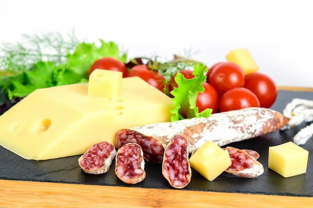 Fromage, fuet et herbes aux tomates sur la planche à tapas, sur l'espace.